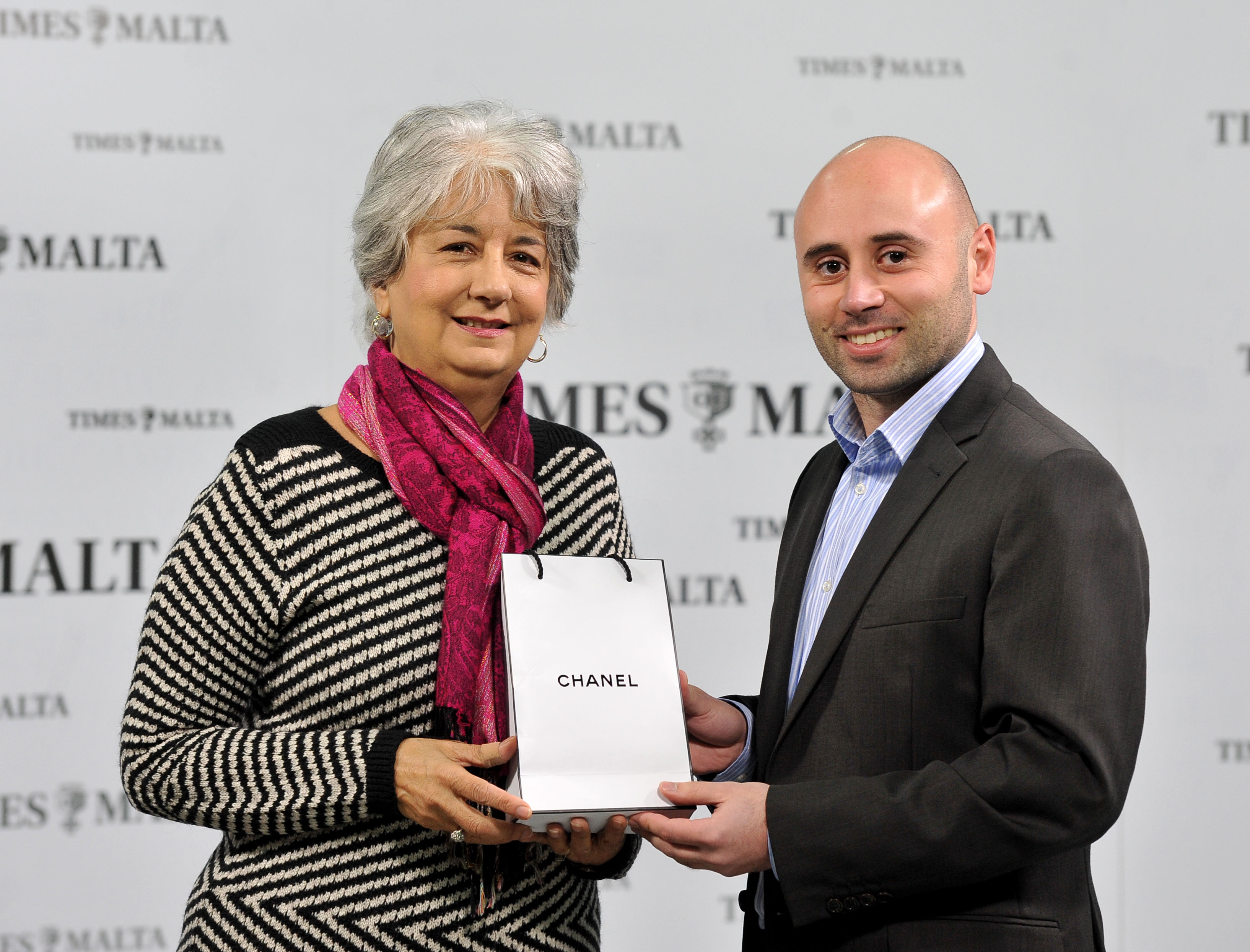 Anne Cachia receives a perfume-for-her courtesy of Chanel from Times of Malta's CCO Alex Galea